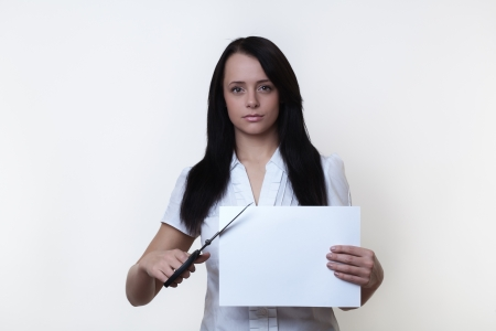 woman cutting the corner of a piece of plain white paper Stock Photo - 14980852