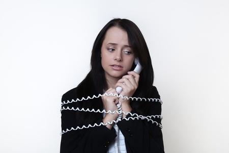 business woman with telephone cord around her tied up on the phone Stock Photo - 14980902