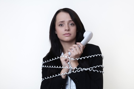 business woman with telephone cord around her tied up on the phone photo