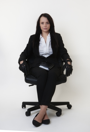 business woman sitting down in a a chair wearing leather driving gloves photo