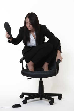 crouched: business woman who doesnt like mice crouched on an office chair looking down at a computer mouse on the floor below her.