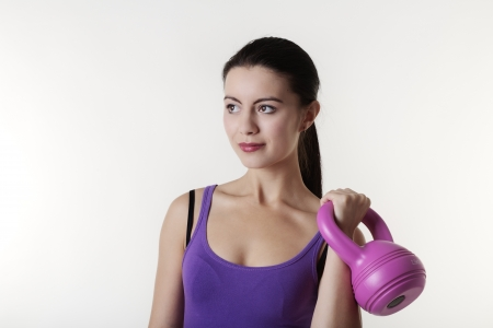young woman working out with a bell weight to keep fit and healthy Stock Photo - 15381180