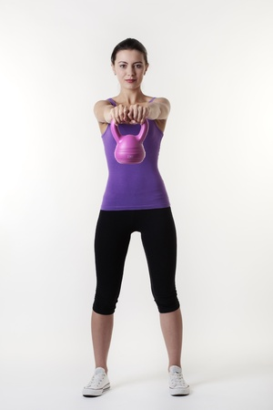 young woman working out with a bell weight to keep fit and healthy Stock Photo - 15380938