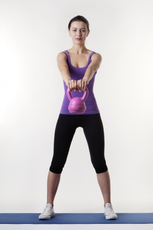 young woman working out with a bell weight to keep fit and healthy
