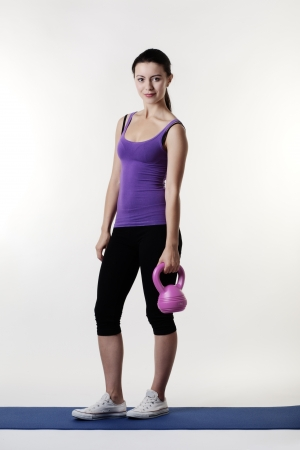 young woman working out with a bell weight to keep fit and healthy Stock Photo - 15381011