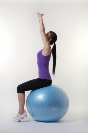 fit ogende jonge vrouw doet stretching oefeningen op een skippybal Stockfoto