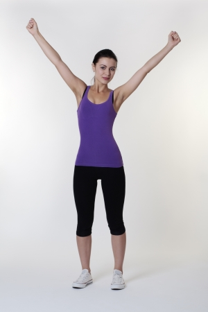woman in exercise clothes with her arms in the air photo