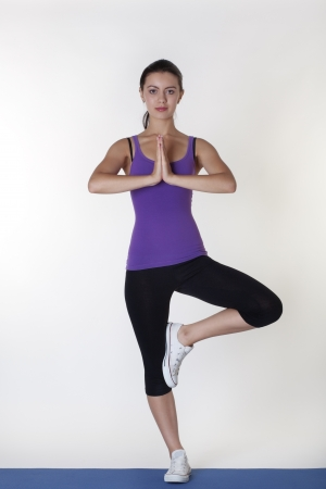 energize: healthy young woman practice yoga, standing in a tree pose