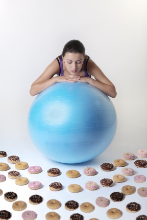attractive woman looking over a exercise gym ball at many donuts unsure what to do the temptation is just to much photo