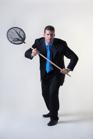 net fishing: business man holding a fishing net trying to find and catch new business Stock Photo