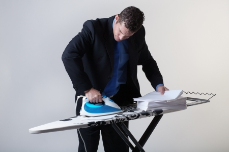 perfectionist: business man ironing out paperwork, keeping good documentations Stock Photo