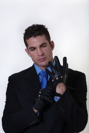 man in a suit putting on gloves getting ready for action