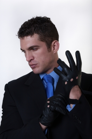 man in a suit putting on gloves getting ready for action photo