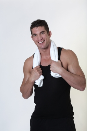 happy smiling good looking male bodybuilder just done a work out with a towel around his neck photo