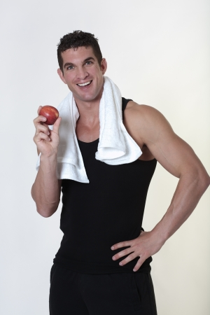 good looking male bodybuilder just done a work out with a towel around his neck about to eat a apple photo