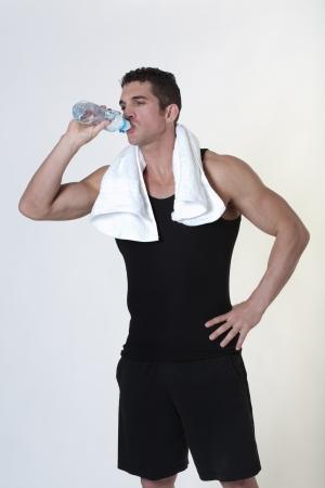 good looking male bodybuilder just done a work out with a towel around his neck drinking water photo