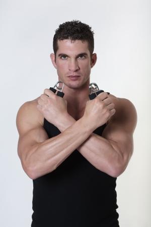 hand gripper: good looking male bodybuilder using hand gripper