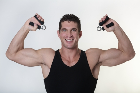 good looking male bodybuilder using hand gripper