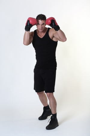 good looking man wearing boxing gloves and working out photo