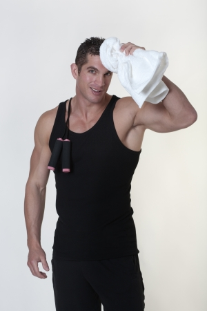 male bodybuilder with a skipping rope around his neck after a good work out wiping his brow with a towel Stock Photo - 15811551