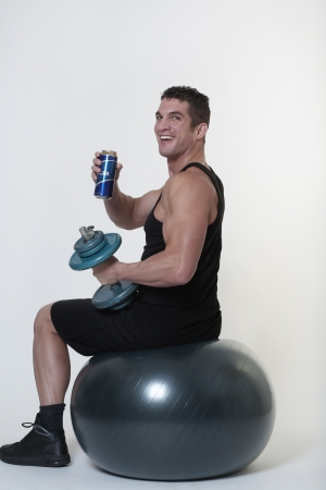 tempted: man sitting on a gym ball being tempted to give up and have a drink Stock Photo