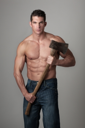 bodybuilder man: good looking male holding a well used axe to chop wood with Stock Photo