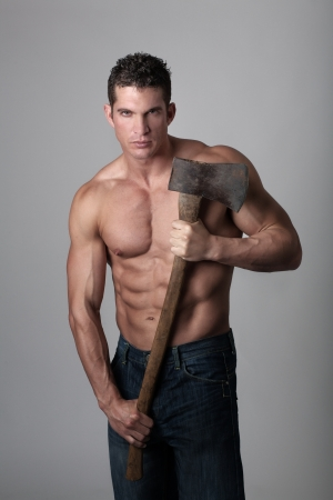 good looking male holding a well used axe to chop wood with photo