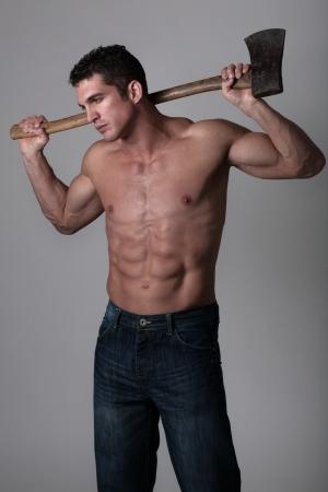 goed uitziende man die een goed gebruikte bijl om hout te hakken met Stockfoto