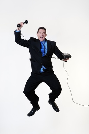 business man jumping in the air very happy and a smile on his face holding a telephone photo
