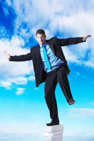 businessman standing on a large pile of paper going right up into the sky photo