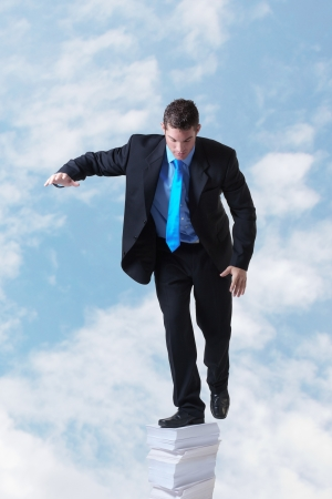 insurmountable: businessman standing on a large pile of paper going right up into the sky