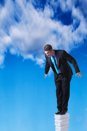 daunting: businessman standing on a large pile of paper going right up into the sky