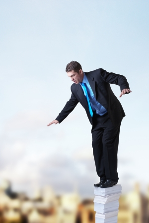 regulate: businessman standing on top of a pile of paper againts a city backdrop