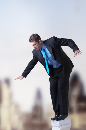 insurmountable: businessman standing on top of a pile of paper against a city backdrop Stock Photo