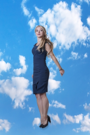 young attractive woman jumping in the air looking very happy against a blue sky background photo