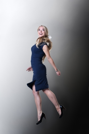 young attractive woman jumping in the air looking very happy against studio background photo