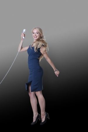 young attractive woman jumping in the air looking very happy against studio background holding a telephone photo