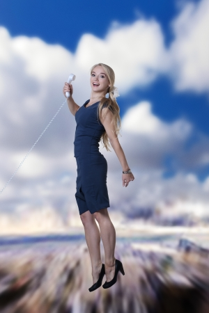 young attractive woman jumping in the air looking very happy against a city sky background holding a telephone photo