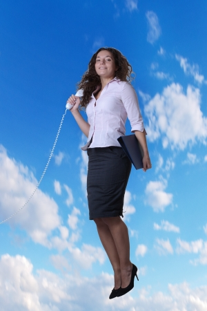 elated: woman jumping in the air holding a telephone looking at the camera