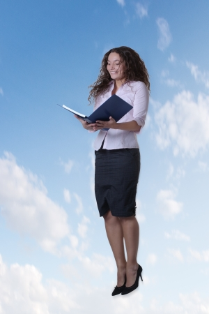elated: woman jumping in the air read a large note book Stock Photo