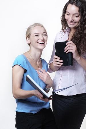 deux collègues de travail à la recherche de quelque chose dans un cahier grand, une femme est mort de rire s'amuser