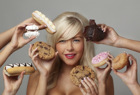 sexy woman surrounded  by many hands holding cream cakes with so much choice and temptation is she going to forget about her diet and indulge herself  photo