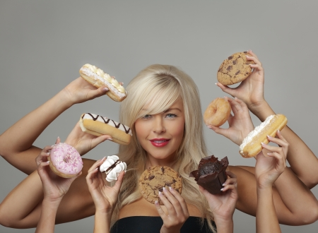 unhealthy snack: sexy woman surrounded  by many hands holding cream cakes with so much choice and temptation is she going to forget about her diet and indulge herself