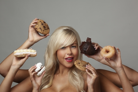 sexy woman surrounded  by many hands holding cream cakes with so much choice and temptation is she going to forget about her diet and indulge herself  Stock Photo - 16615933