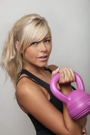 keeping fit: sexy woman keeping fit using a kettlebell weight to train with