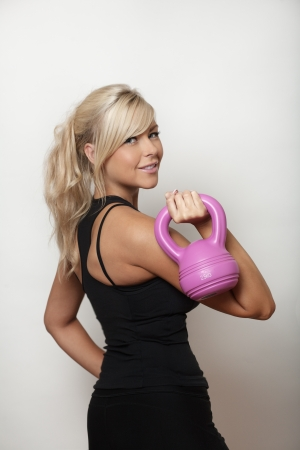 sexy woman keeping fit using a kettlebell weight to train with photo