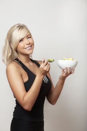 sexy woman eating from a bowl of fresh fruit photo