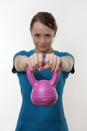 attractive woman doing a workout routine with a  kettlebell weight Stock Photo - 17079898