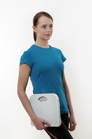 Fit young woman with holding scales  Stock Photo - 17079828