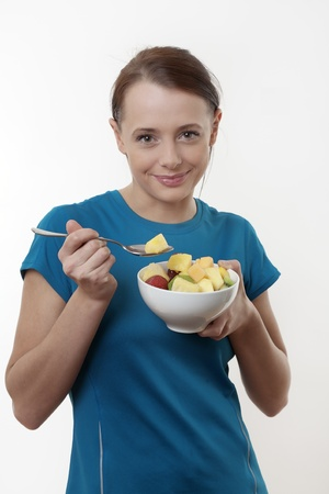 Thoughtful  woman eating a fruit salad looking very happy Stock Photo - 17079736